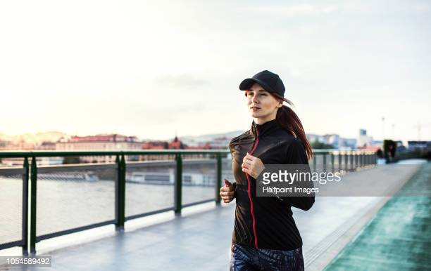 A sporty young woman running on the bridge outdoors in the city.