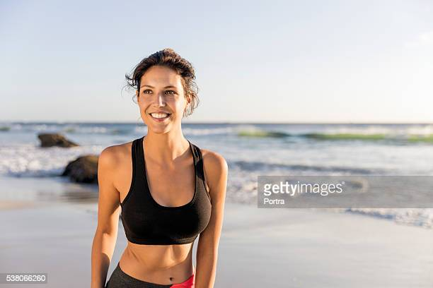 sporty young woman smiling at beach - mid adult stock pictures, royalty-free photos & images