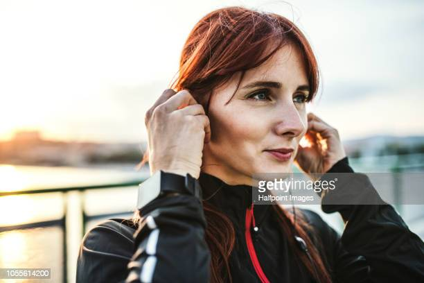A sporty young woman standing on the bridge outdoors in city, putting earphones in her ears.