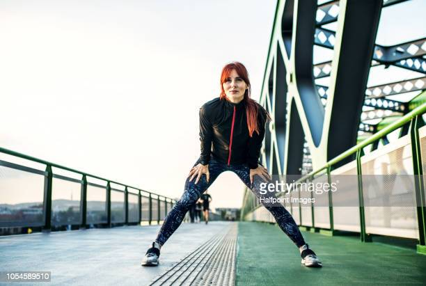 A sporty young woman stretching on the bridge outdoors in the city.