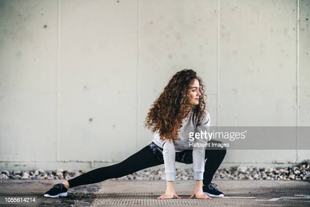 A sporty young woman stretching under the bridge outdoors in the city.