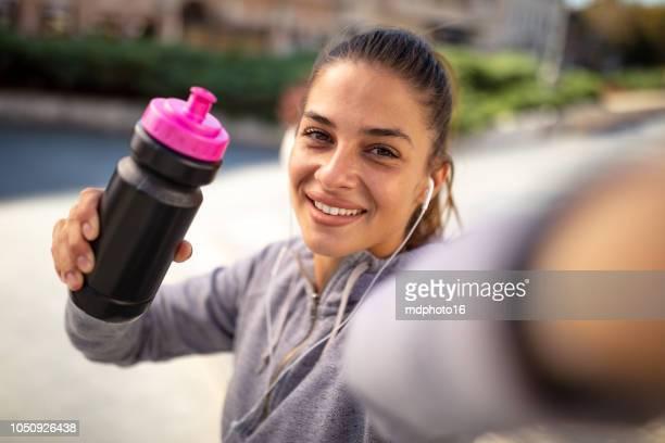 sportliche junge frau, die unter einem selfie während der bewegung in der natur - selbstporträt stock-fotos und bilder