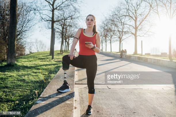 sporty young woman with leg prosthesis holding cell phone - leaning disability stock pictures, royalty-free photos & images