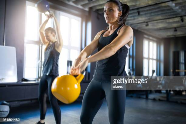 sporty young women swinging kettlebells in gym - crossfit stock pictures, royalty-free photos & images