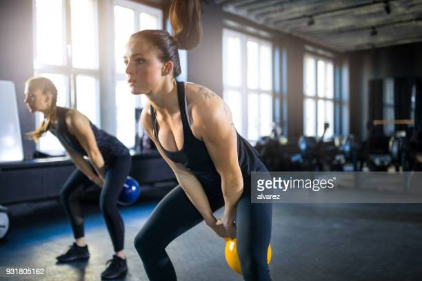 mulheres jovens desportivos balançando kettlebells no ginásio - kettlebell - fotografias e filmes do acervo