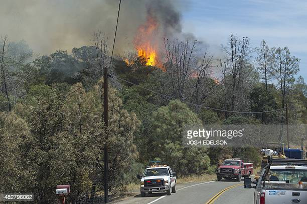 A spot fire sends flames from the Rocky fire into the air as fire personnel arrive on the scene near Clear lake California on August 02 2015...