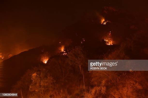 Spot fires burn on the hills above Pepperdine University during the Woolsey fire November 12 2018 in Malibu California Another three firefighters...