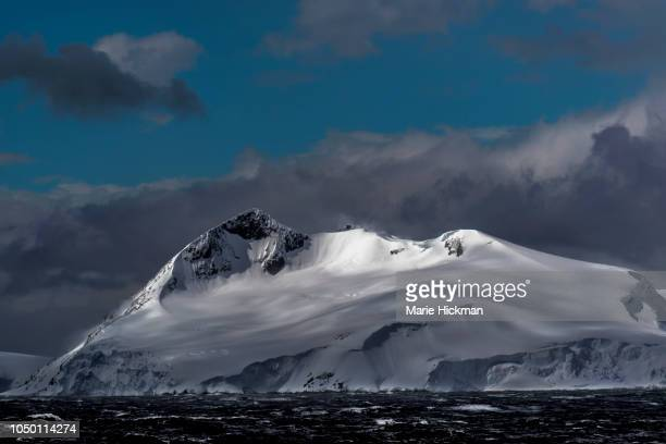 spot light on snow-capped mountain peak in antarctica. - antarctic peninsula stock pictures, royalty-free photos & images