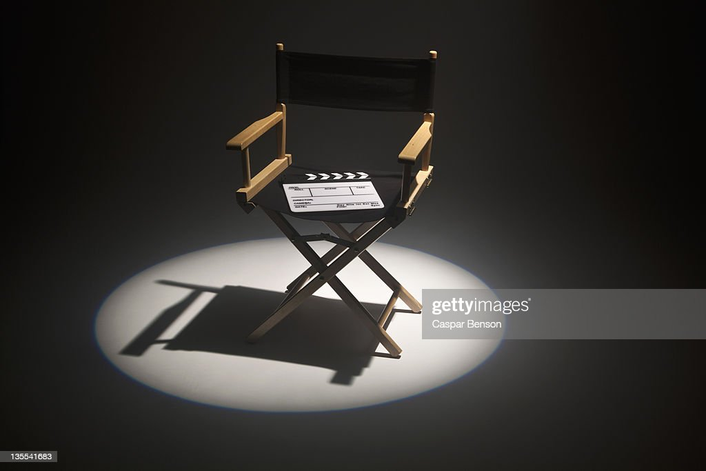 A spot lit directors chair and a clapper board : Stock Photo