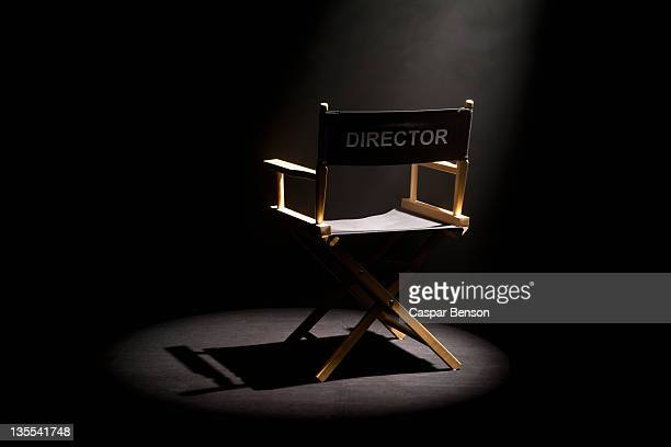 a spot lit directors chair - film studio stock pictures, royalty-free photos & images