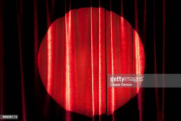 a spot lit red stage curtain - stage curtain stock pictures, royalty-free photos & images