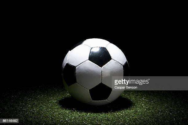 a spot lit soccer ball on turf - turf stock pictures, royalty-free photos & images