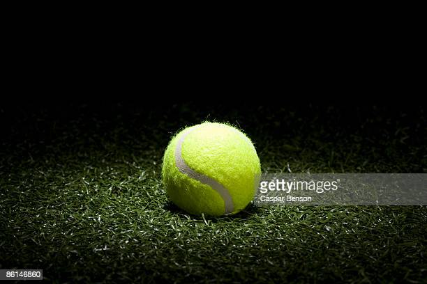 A spot lit tennis ball on turf