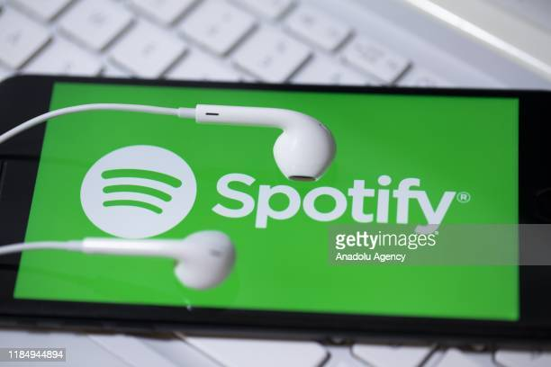 Spotify logo is being displayed in a smart phone and an earphone is seen in Ankara Turkey on November 26 2019