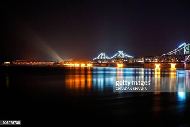 TOPSHOT Spotlight beams are seen from the North Korean town of Sinuiju past Friendship Bridge and Broken Bridge as seen from Dandong China's...