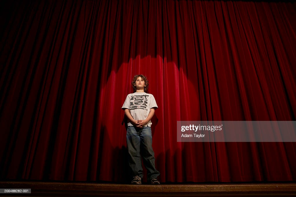 Spotlight On Boy 10 12 Standing Stage Curtains Low Angle View