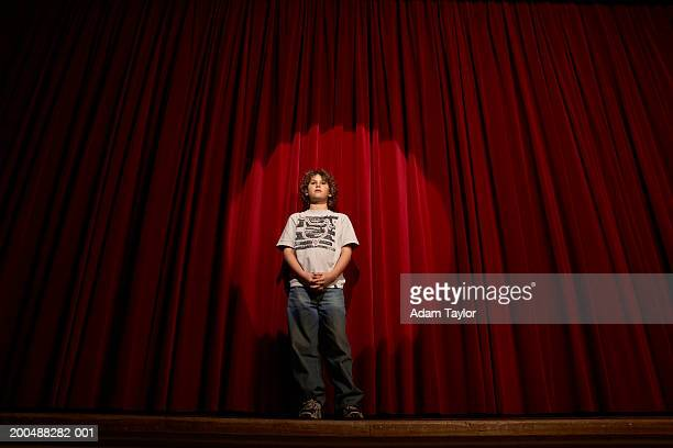 spotlight on boy (10-12)  standing on stage curtains, low angle view - あがり症 ストックフォトと画像