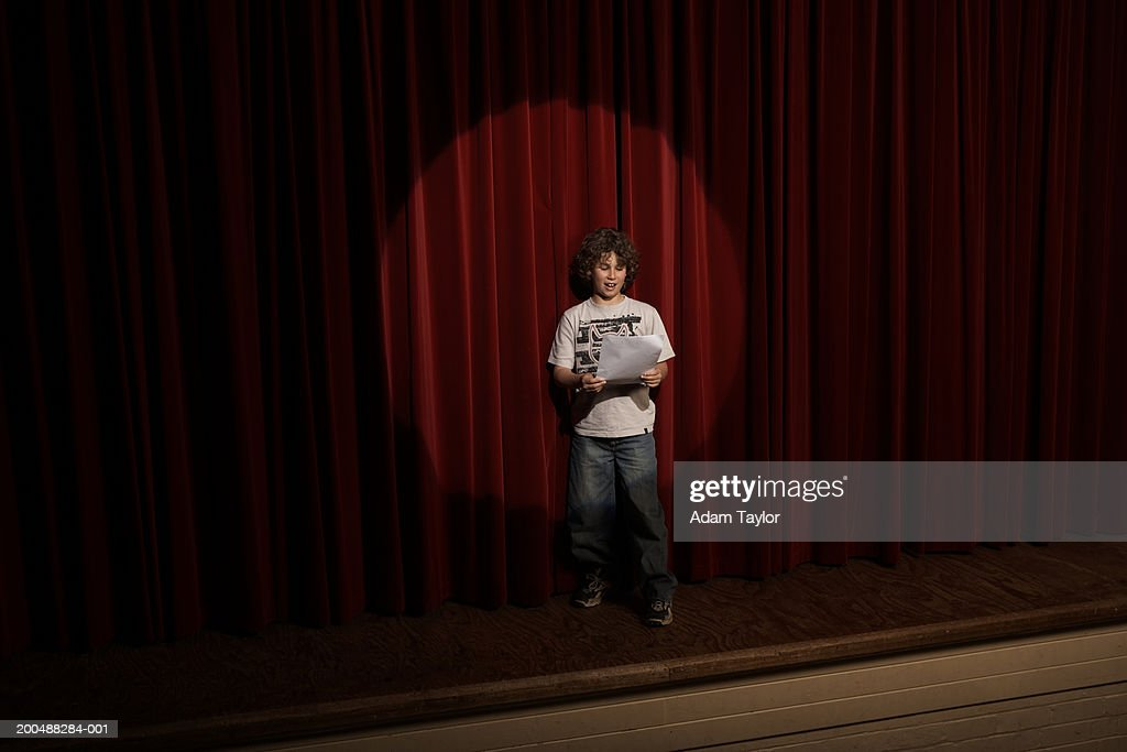 Spotlight on boy (10-12)  standing on stage, reading lines : Stock Photo