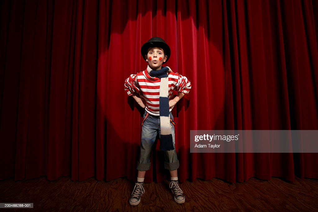 Spotlight on boy (8-10)  wearing clown outfit, hands on hips, portrait : Stock Photo