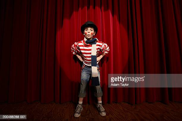 Spotlight on boy (8-10)  wearing clown outfit, hands on hips, portrait