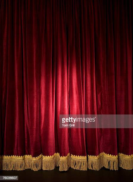 spotlight on closed red stage curtain - stage curtain stock pictures, royalty-free photos & images