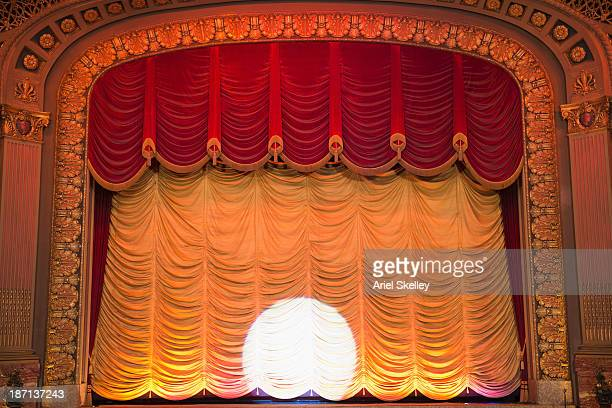 spotlight on curtain in ornate movie theater - stage curtain stock pictures, royalty-free photos & images