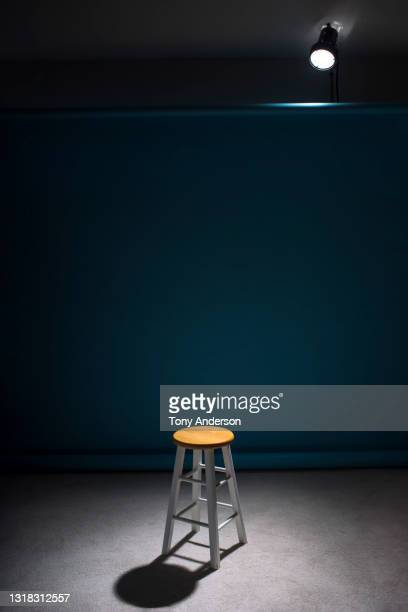 spotlight on empty stool on stage - photo shoot stock pictures, royalty-free photos & images