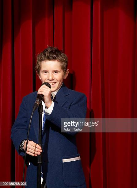 Spotlight on on boy (11-13) using microphone on stage, portrait