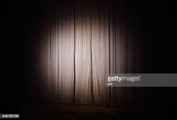 spotlight on stage curtain - spotlit stock pictures, royalty-free photos & images