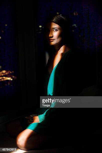 Spotlight on woman in front of window