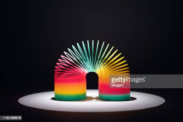 spotlit colorful coil toy - espiral de metal - fotografias e filmes do acervo