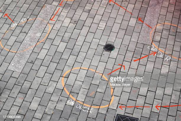 Spots are marked in chalk for patrons to stay six feet apart while shopping at the Safe Supply outdoor grocery store at Bow Market on March 21 2020...