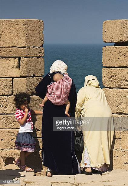 Spotted on the battlement walls of Essaouira, a family taking in the views while the young girl seems bored with it all! It amused me at the time, -...