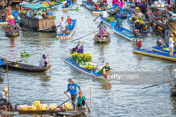 spouses boatman selling daisies, watermelons on the river - mekong delta stock pictures, royalty-free photos & images