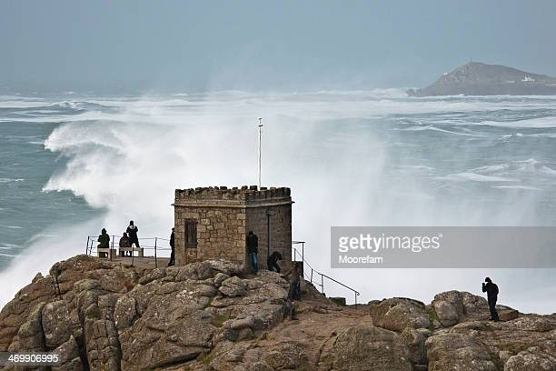 Spray from large wave towers above onlookers at Sennen Cornwall