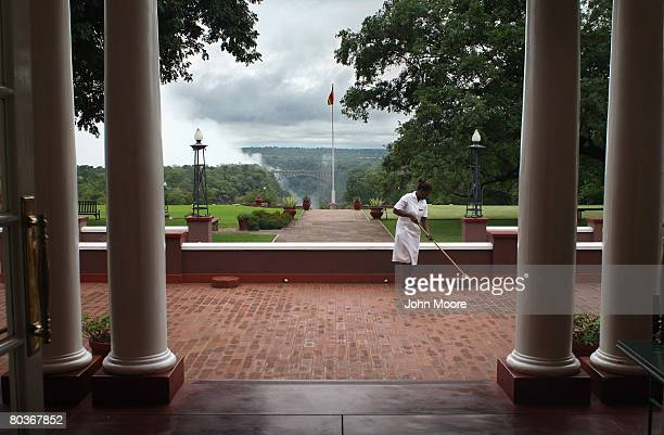 Spray from Victoria Falls shoots into the air in the distance as a maid cleans the terrace of the historic Victoria Falls Hotel March 18 2008 at...
