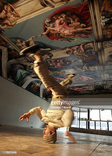 Spray paint artist and break dancer Paco Rosic shows off his famous head spin by the 81 feet by 31 feet abstract representation of Michelangelo's...
