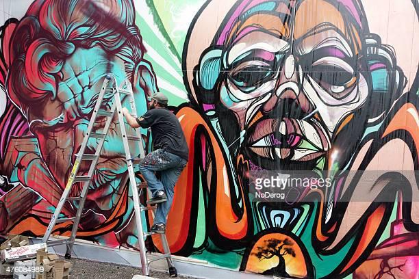 Spray paint artist works on building mural.