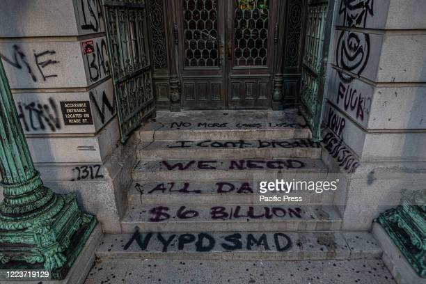 Spray painted vandalism is seen as hundreds of protesters occupy the space around City Hall awaiting details on how Mayor Bill de Blasio proposes to...