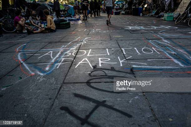 Spray painted vandalism is seen as hundreds of protesters occupy the space around City Hall, awaiting details on how Mayor Bill de Blasio proposes to...