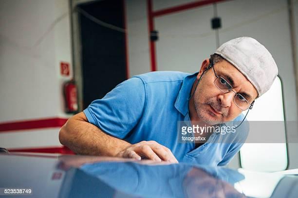 Lackierer inspects seine Arbeit