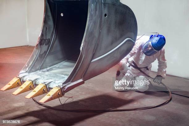 spray painter painting digger bucket in spray booth in engineering factory - monty shadow - fotografias e filmes do acervo
