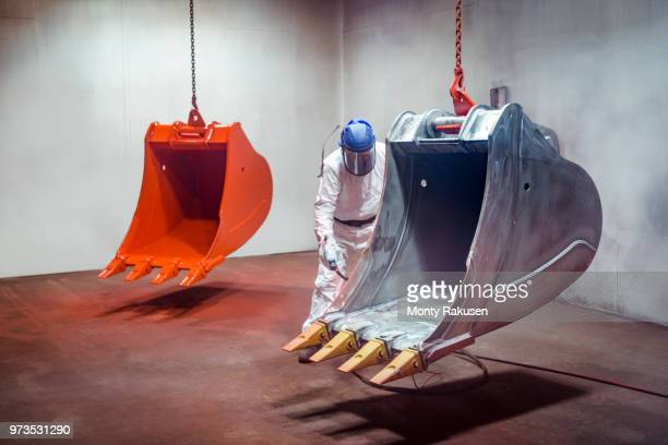 spray painter painting digger buckets in spray booth in engineering factory - monty shadow - fotografias e filmes do acervo