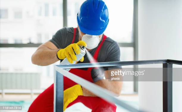 spray painting a metal table frame. - spray paint stock pictures, royalty-free photos & images