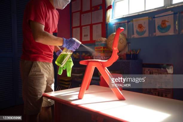 spruzzatura su mobili per bambini con soluzione detergente - servizi per l'infanzia foto e immagini stock