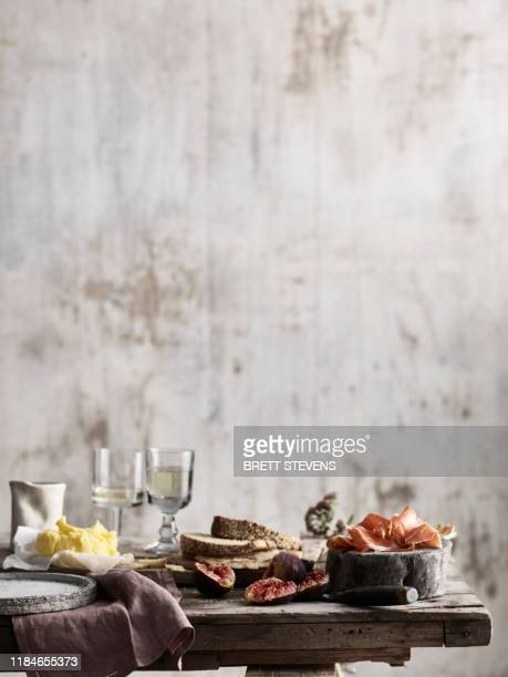 spread of bread, butter, figs and ham on table - still life foto e immagini stock