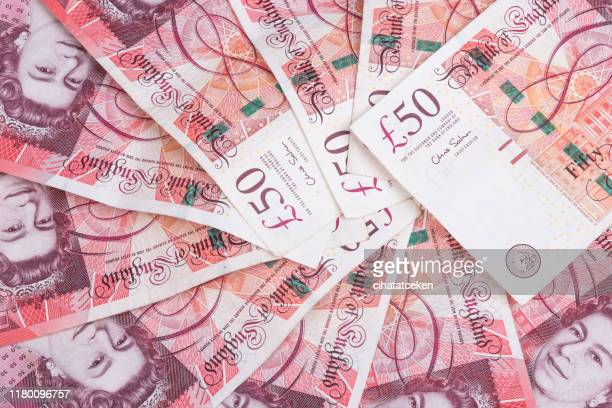 spread of random 50 british pound notes - fifty pound note stock pictures, royalty-free photos & images
