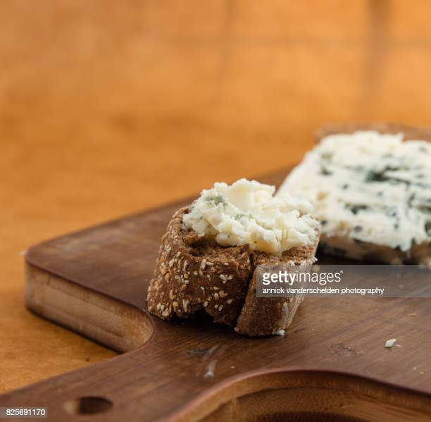 spread roquefort cheese on cut baguette piece. - clamidia fotografías e imágenes de stock