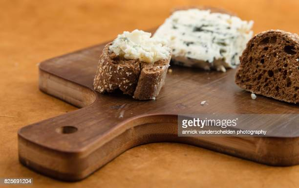 spread roquefort cheese on cut baguette piece. - roquefort cheese stock photos and pictures