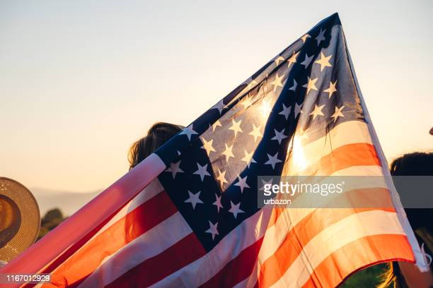 spreading american flag - fourth of july stock pictures, royalty-free photos & images